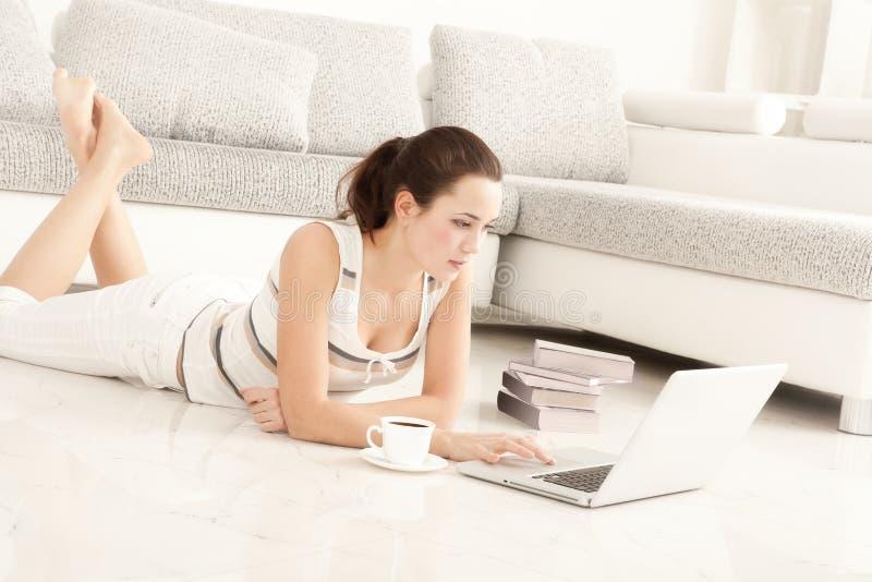Ung kvinna som surfar internet med bärbara datorn fotografering för bildbyråer