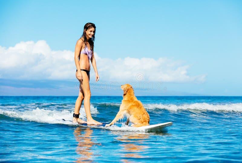 Ung kvinna som surfar med hennes hund fotografering för bildbyråer