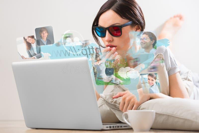 Ung kvinna som surfar på rengöringsduk med den moderna bärbara datorn arkivfoto