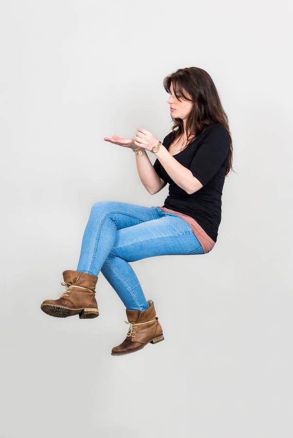 Ung kvinna som svävar i sammanträdeposition med att framlägga gest royaltyfri bild