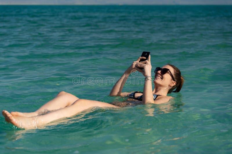 Ung kvinna som svävar på vattenyttersidan av det döda havet och använder hennes smartphone royaltyfria foton