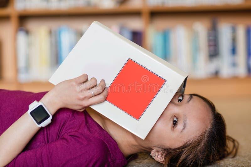 Ung kvinna som täcker hennes framsida med boken arkivbild