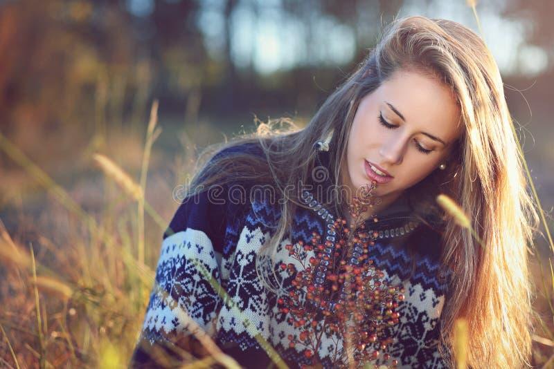 Ung kvinna som tänker i höstäng arkivbild