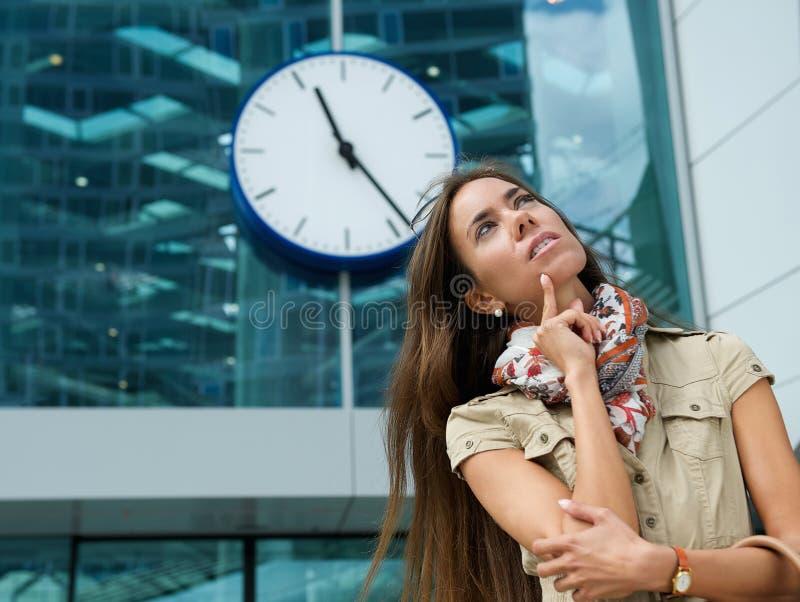 Ung kvinna som tänker med klockan i bakgrund royaltyfri fotografi