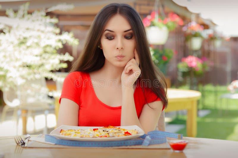 Ung kvinna som tänker om att äta pizza på en banta arkivbilder