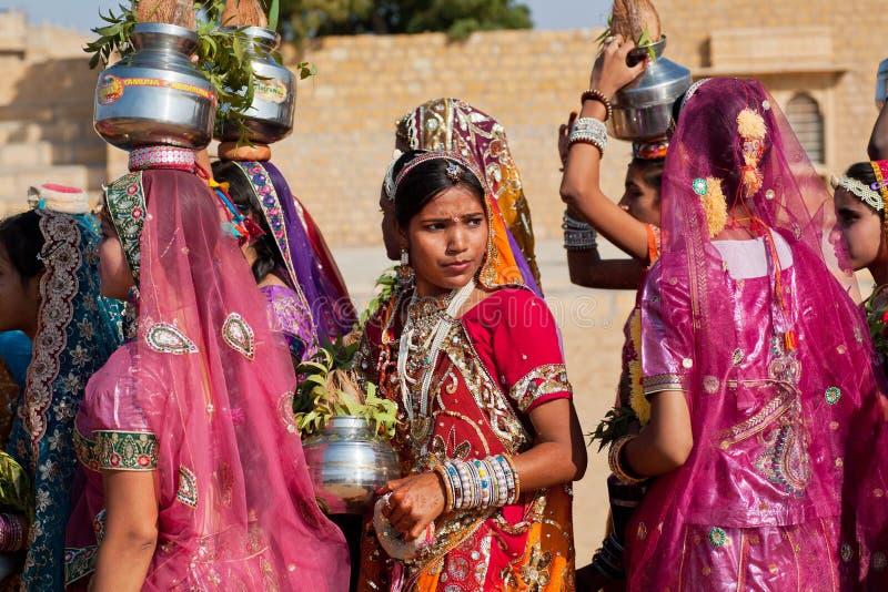 Ung kvinna som tänker om något i en folkmassa av den iklädda sari för flickor arkivfoton