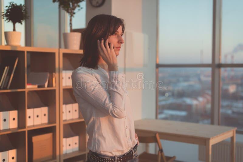 Ung kvinna som talar genom att använda mobiltelefonen på kontoret i aftonen Koncentrerad kvinnlig affärskvinna och att se framåtr royaltyfri fotografi