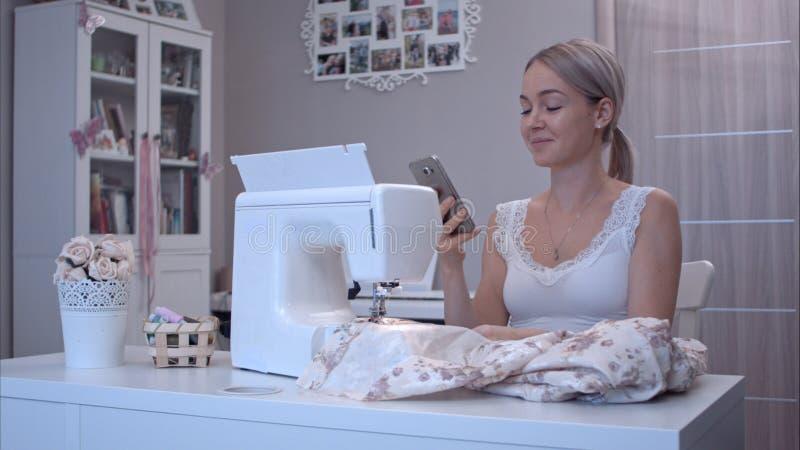 Ung kvinna som talar lyckligt på telefonen, medan sitta på tabellen bredvid symaskinen arkivfoto