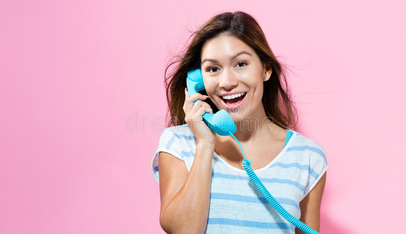 Ung kvinna som talar på den gamla modetelefonen arkivbilder