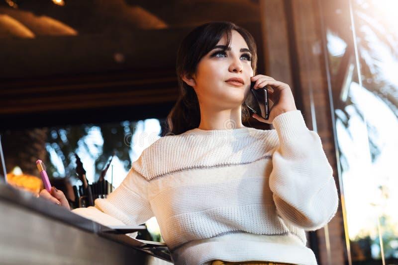 Ung kvinna som talar på mobiltelefonen, medan sitta bara i coffee shop När du ler flickan har telefonkonversation, medan vila i k royaltyfri fotografi
