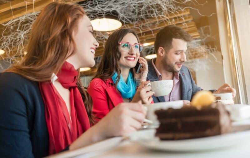 Ung kvinna som talar på mobiltelefonen, medan tycka om en kopp kaffe arkivbilder