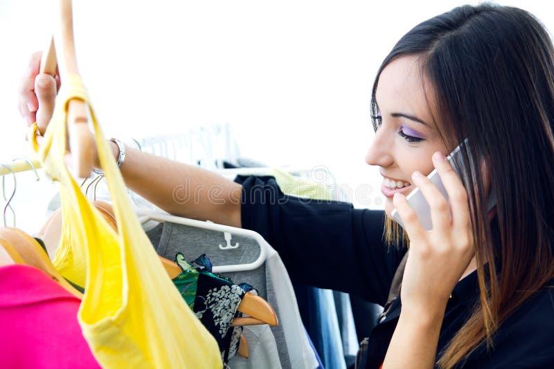 Ung kvinna som talar på telefonen, medan shoppa för kläder royaltyfria foton