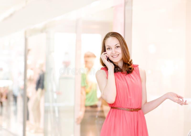Ung kvinna som talar på telefonen på gallerian royaltyfria bilder