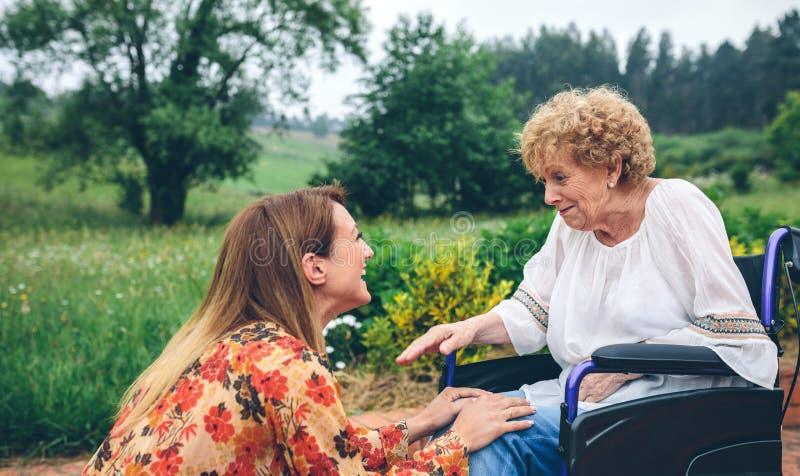 Ung kvinna som talar till den äldre kvinnan i en rullstol royaltyfria foton