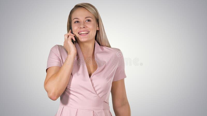 Ung kvinna som talar till någon på hennes mobiltelefon på lutningbakgrund arkivfoto