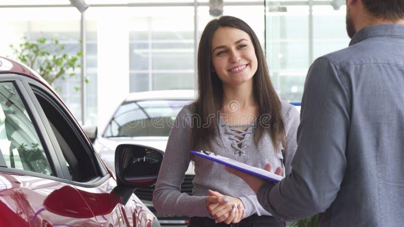 Ung kvinna som talar till representanten på bilåterförsäljaren royaltyfri fotografi
