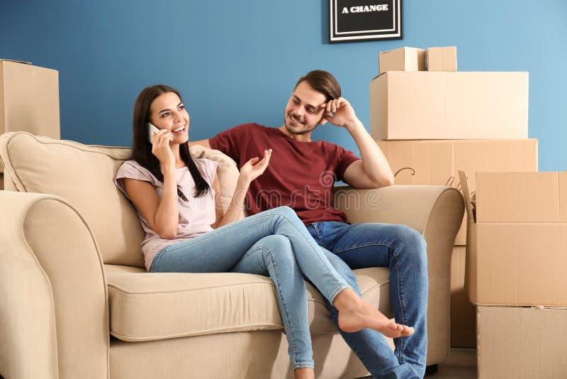 Ung kvinna som talar vid mobiltelefonen medan hennes make som sitter på soffan på det nya hemmet arkivbild