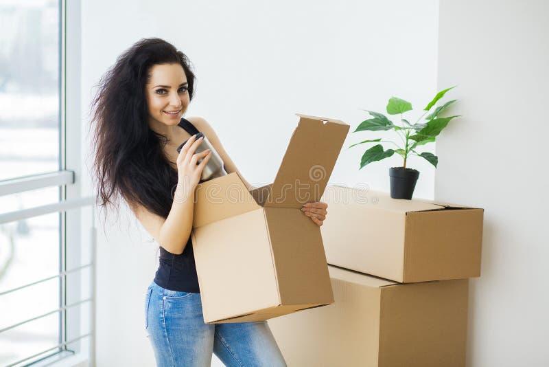 Ung kvinna som tappar kartongen home flytta sig som är nytt arkivfoto