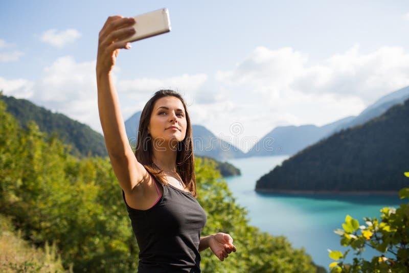 Ung kvinna som tar bilder på telefonen royaltyfri fotografi