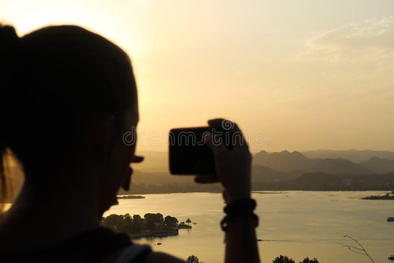 Ung kvinna som tar en bild av den härliga solnedgången i Udaipur arkivfoton