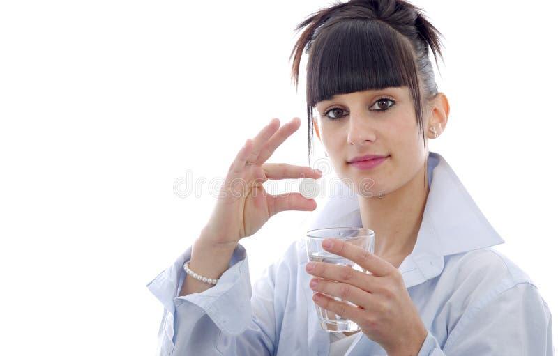 Ung kvinna som tar en preventivpiller, på vit arkivbild