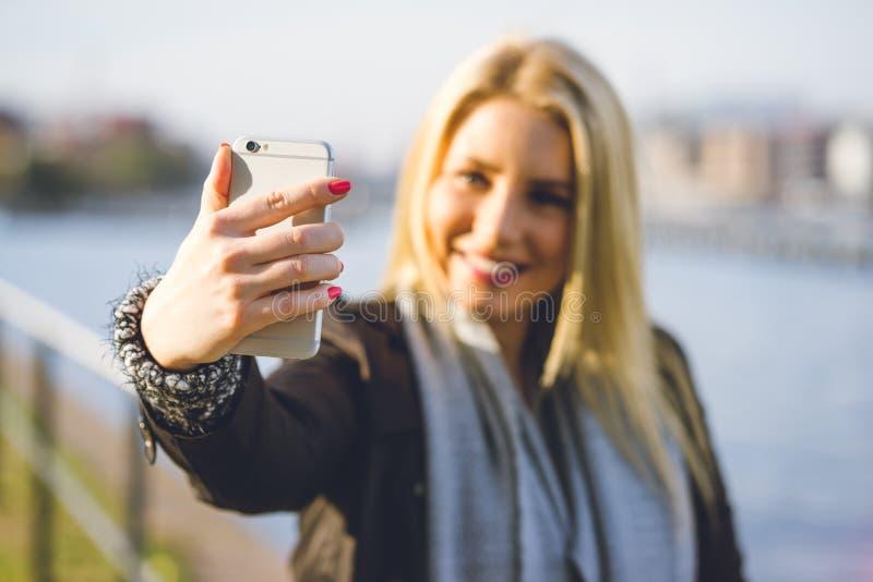 Ung kvinna som tar en selfie i höstsolen arkivbilder
