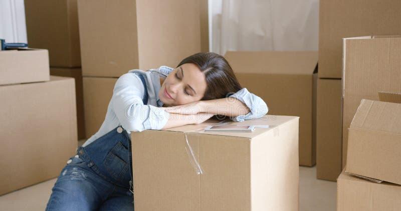 Ung kvinna som tar en ta sig en tupplur på en brun låda royaltyfria foton