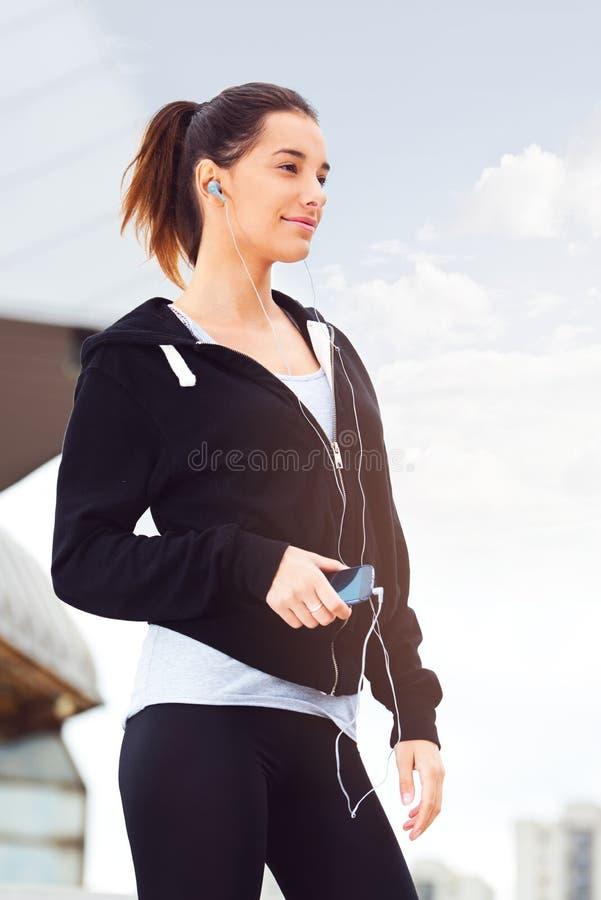 Ung kvinna som tar ett avbrott från att öva utanför arkivfoton