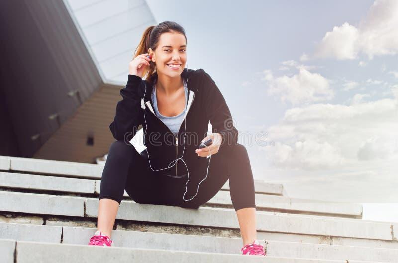 Ung kvinna som tar ett avbrott från att öva utanför med mobiltelefonen fotografering för bildbyråer