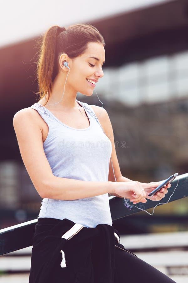 Ung kvinna som tar ett avbrott från att öva utanför med mobiltelefonen royaltyfri bild