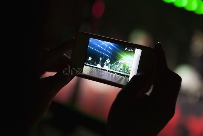 Ung kvinna som tar ett fotografi med hennes smarta telefon på en inomhus konsert, närbild på händer arkivfoton