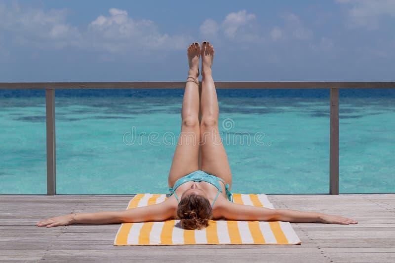 Ung kvinna som tar ett solbränt på en terrass Klart bl?tt vatten som bakgrund fotografering för bildbyråer