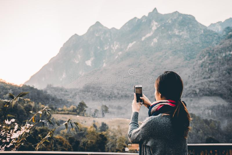 Ung kvinna som tar fotoet med hennes telefon av den härliga bergsikten royaltyfria foton