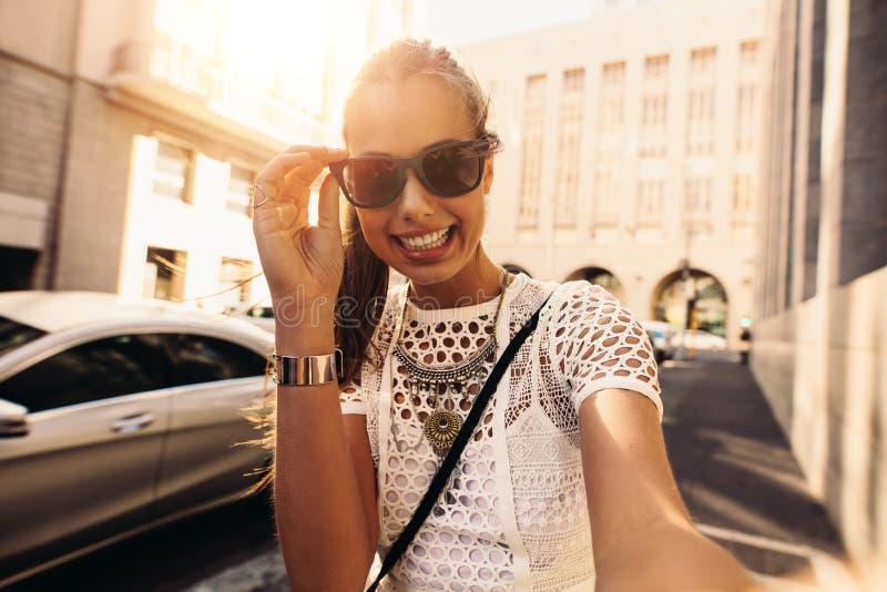 Ung kvinna som tar selfie i en gata som omges av byggnader arkivfoton