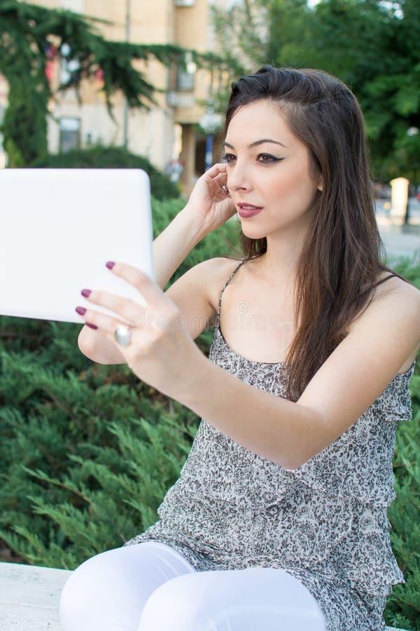 Ung kvinna som tar selfie med en minnestavla arkivbild