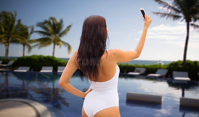 Ung kvinna som tar selfie med smartphonen på stranden royaltyfria foton