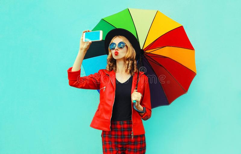 Ung kvinna som tar selfiebilden av smartphonen som blåser röda kanter som överför den söta luftkyssen med det färgrika paraplyet  fotografering för bildbyråer