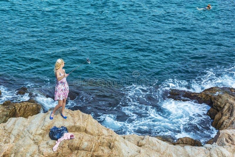 Ung kvinna som tar selfies som står på stenar vid havet Lloret fotografering för bildbyråer