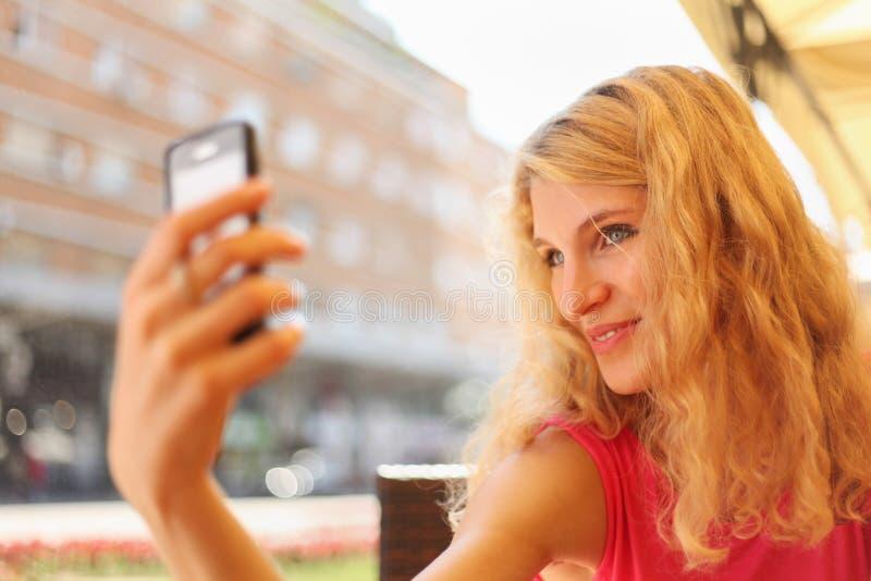 Ung kvinna som tar selfportrait på mobiltelefonen royaltyfri fotografi