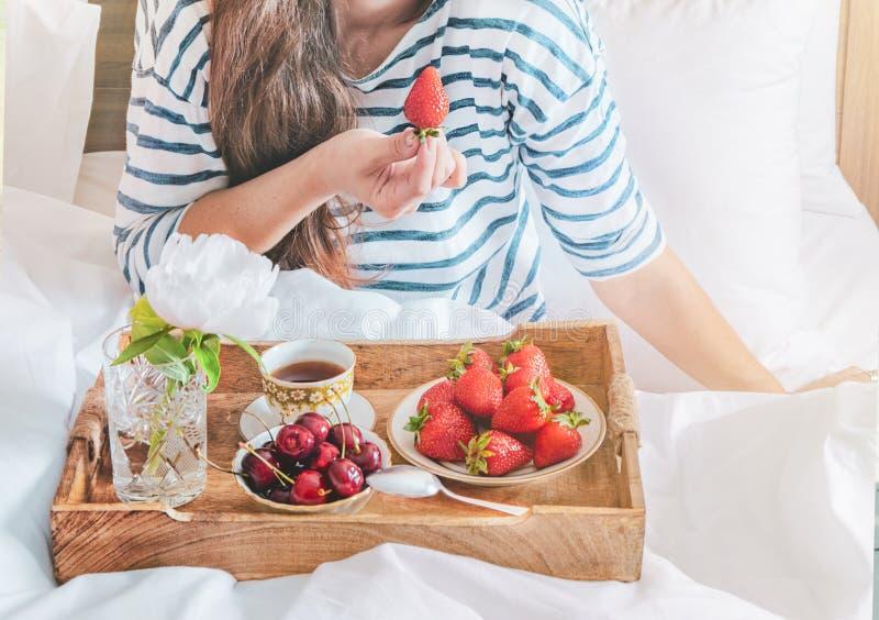 Ung kvinna som ?ter den sunda frukosten i s?ng Romantisk frukost med jordgubbar och den söta körsbäret i en säng arkivfoton