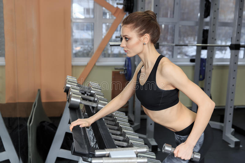 Ung kvinna som tillbaka övar med hantlar i idrottshallen och böjer muskler - muskulös idrotts- kroppsbyggarekonditionmodell arkivbild