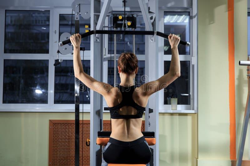 Ung kvinna som tillbaka övar på maskinen i idrottshallen och böjer muskler - muskulös idrotts- kroppsbyggarekonditionmodell arkivbild