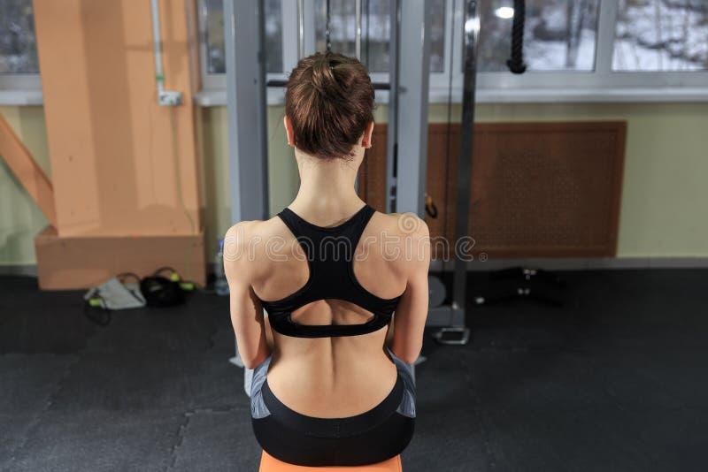 Ung kvinna som tillbaka övar på maskinen i idrottshallen och böjer muskler - muskulös idrotts- kroppsbyggarekonditionmodell royaltyfri fotografi
