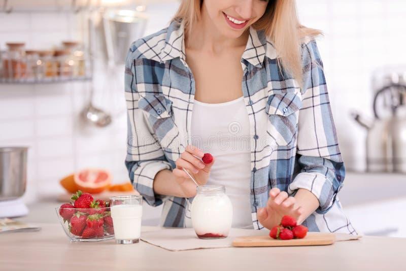 Ung kvinna som tillfogar jordgubben in i kruset med smaklig yoghurt royaltyfri bild