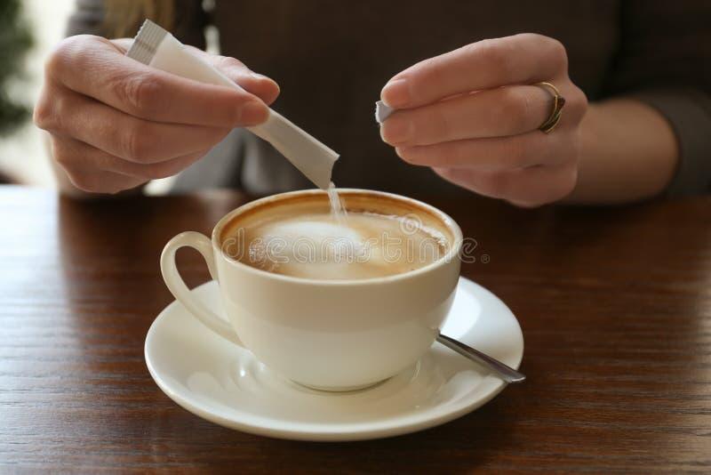 Ung kvinna som tillfogar socker till läckert kaffe royaltyfri fotografi