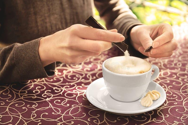Ung kvinna som tillfogar socker till läckert kaffe på tabellen arkivbilder