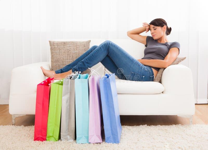 Ung kvinna som tröttas av shopping royaltyfri fotografi