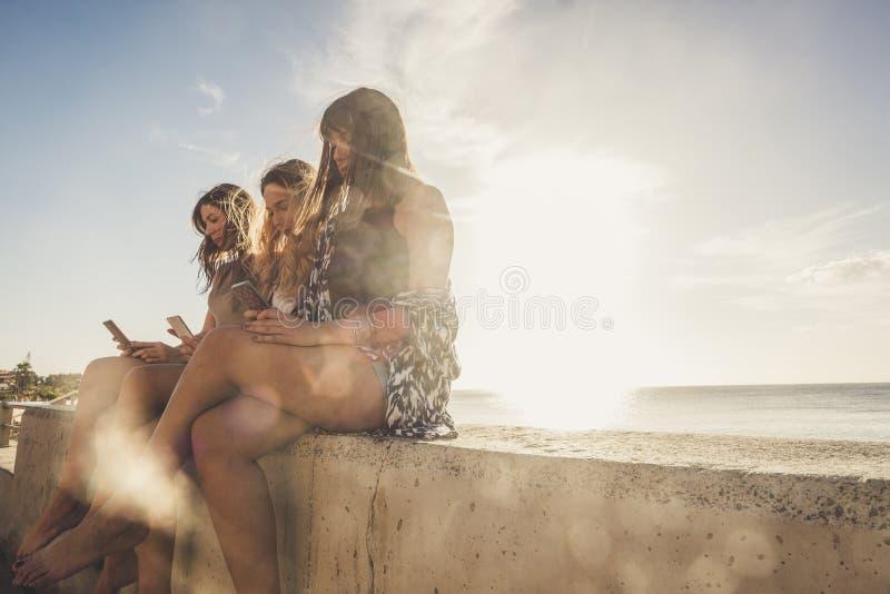 Ung kvinna som tre använder telefonen för att ta selfies i semester nära t royaltyfria bilder