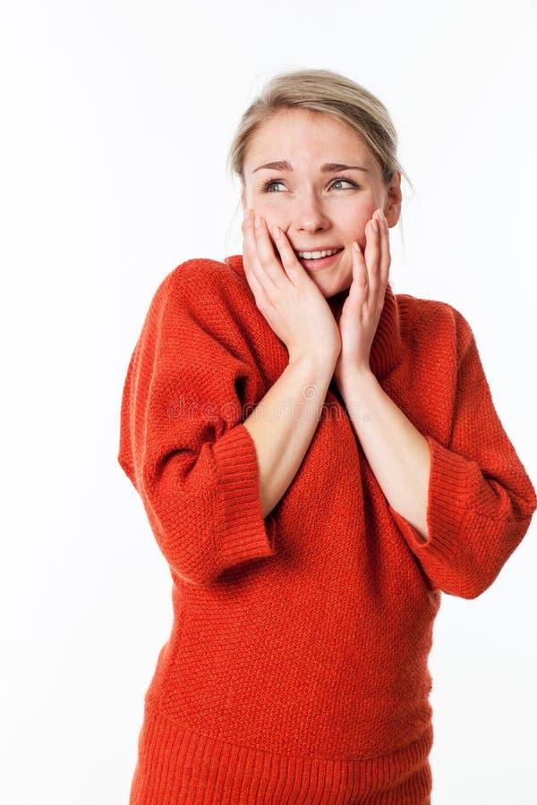 Ung kvinna som trycker på hennes framsida för fröjd och glädje arkivfoto