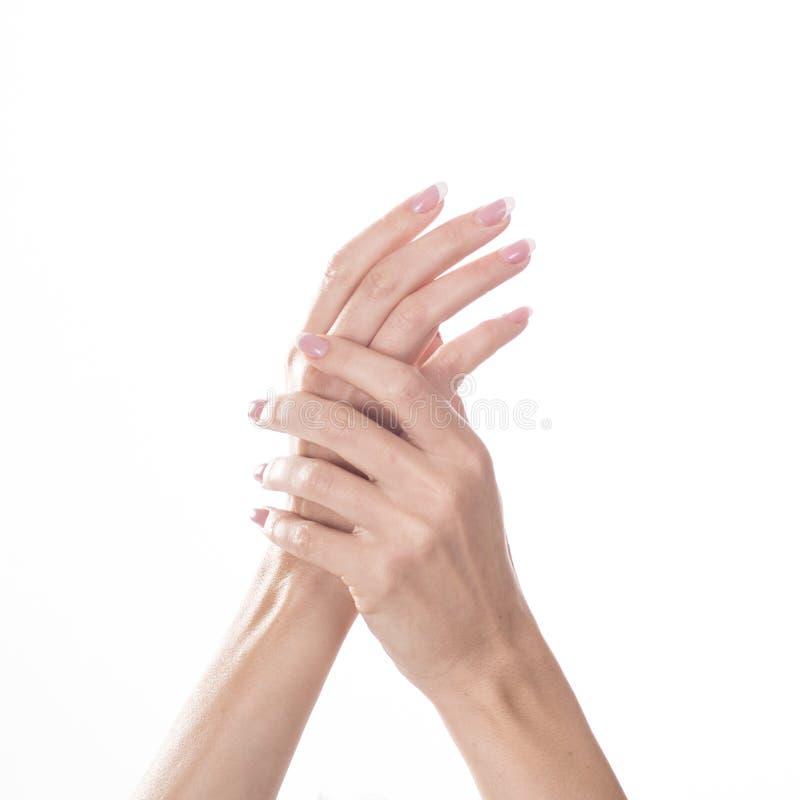 Ung kvinna som trycker på hennes hand och känsla som fuktar effekt av kräm på vit bakgrund arkivbild